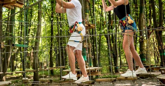 Молодая пара весело проводит время в веревочном парке приключений. альпинистское снаряжение. ношение ремня безопасности и защитных шлемов.