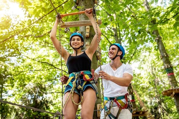Молодая пара весело проводит время в веревочном парке приключений