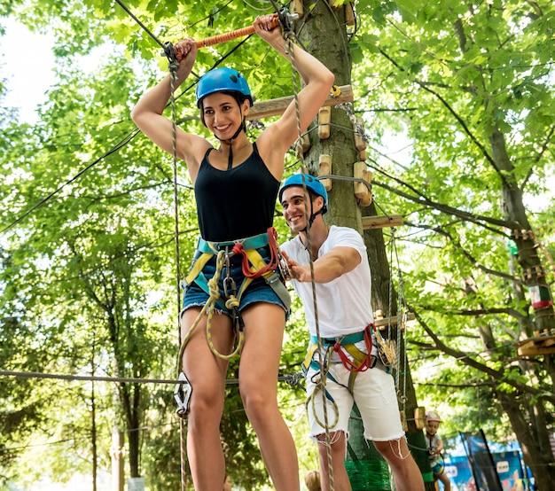 冒険ロープパークで楽しい時間を持っている若いカップル。