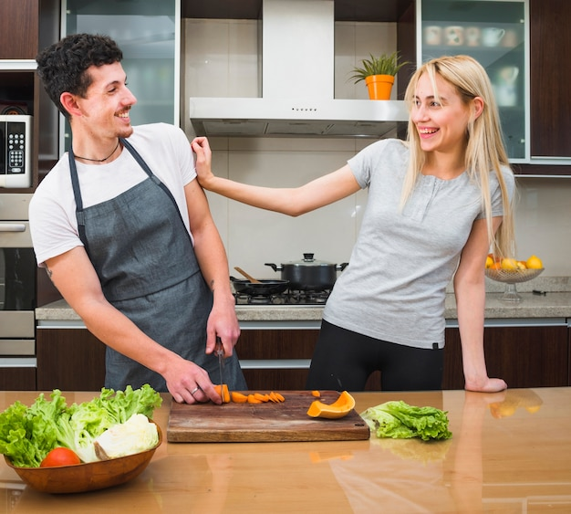 Young couple having fun while cutting vegetables in the kitchen