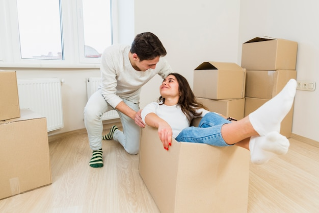 Young couple having fun while moving to a new apartment