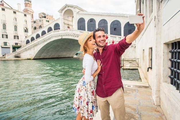 Молодая пара веселится во время посещения венеции - туристы, путешествующие по италии и осматривающие самые важные достопримечательности венеции - концепции образа жизни, путешествий, туризма