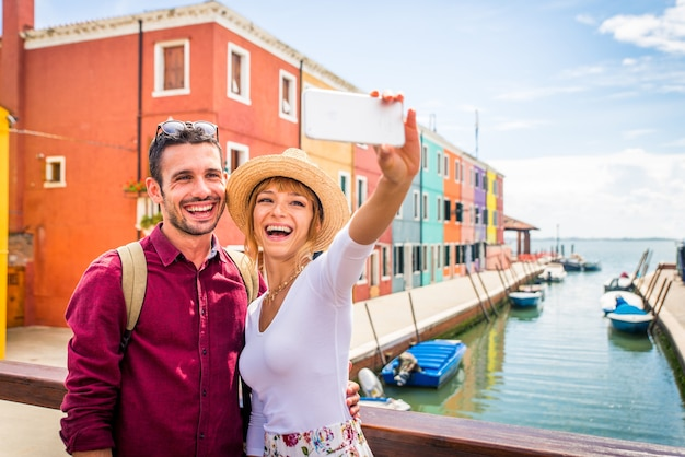 Young couple having fun while visiting venice - tourists travelling in italy and sightseeing the most relevant landmarks of venezia - concepts about lifestyle, travel, tourism