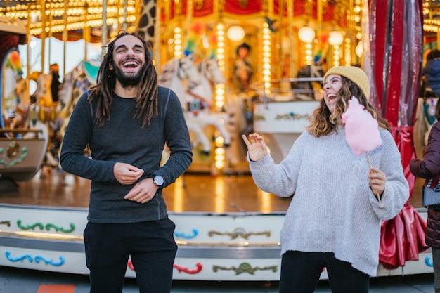 Молодая пара веселится с сахарной ватой на рождественской ярмарке