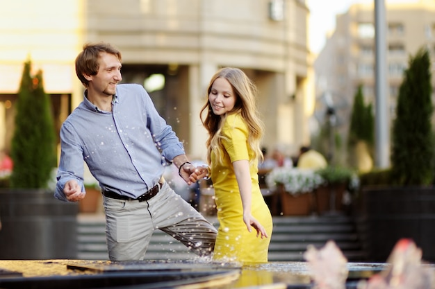 Young couple having fun with a city fountain