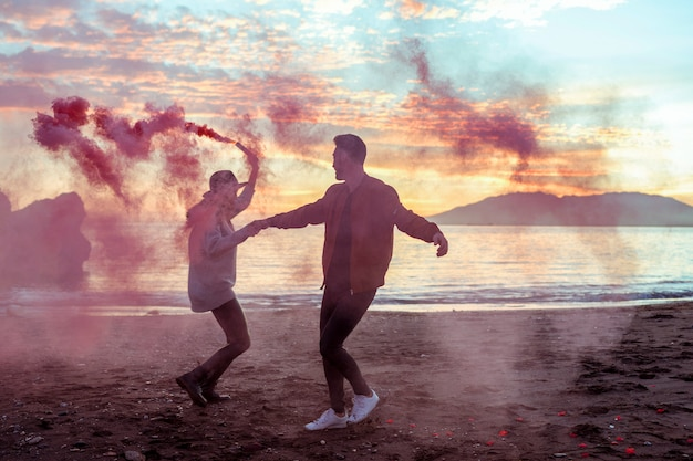 Young couple having fun with pink smoke bomb on sea shore