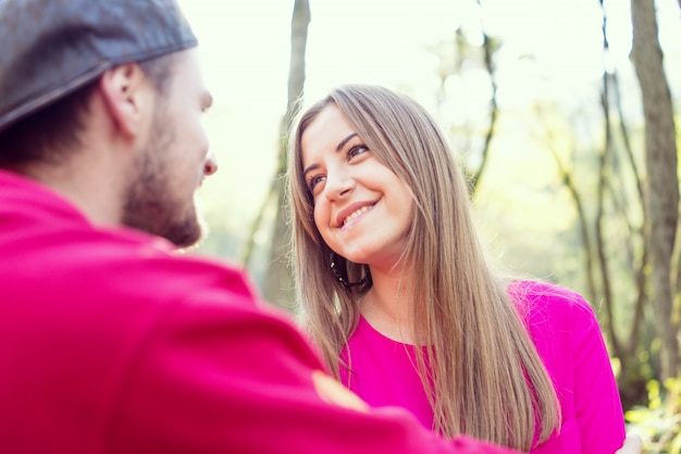 Young couple having good time together in park on river