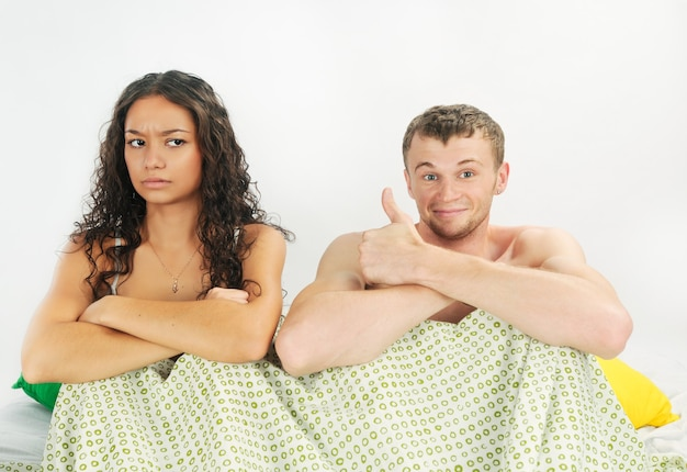 Young couple having happy leisure time in bed