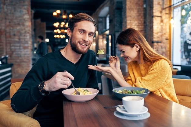 カフェのテーブルで昼食をとっている若いカップル