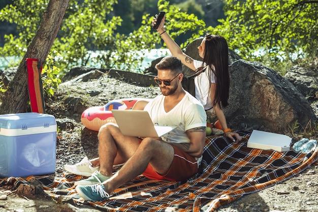 Молодая пара, пикник на берегу реки в солнечный день. женщина и мужчина вместе проводят время на природе. веселиться, есть, играть и смеяться. концепция отношений, любви, лета, выходных.