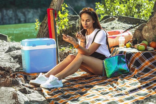 晴れた日に川沿いでピクニックをしている若いカップル。一緒に自然に時間を費やす女性と男性。楽しんで、食べて、遊んで、笑って。関係、愛、夏、週末の概念。