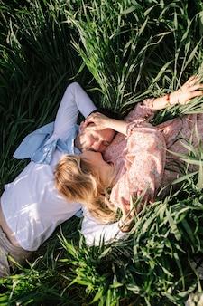 明るい晴れた日に牧草地でピクニックをしている若いカップル。男と女はお互いの会社を楽しんでいます
