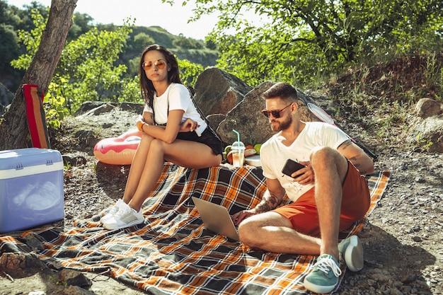 Giovani coppie che hanno picnic in riva al fiume in una giornata di sole. donna e uomo che trascorrono del tempo insieme sulla natura. divertirsi, mangiare, giocare e ridere. concetto di relazione, amore, estate, fine settimana.