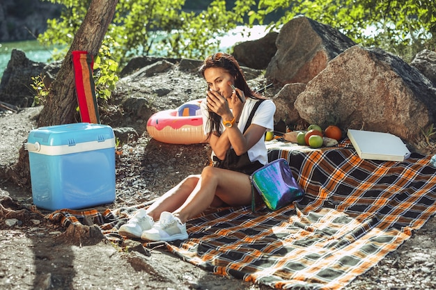 Young couple having picnic at riverside in sunny day. woman and man spending time on the nature together. having fun, eating, playing and laughting. concept of relationship, love, summer, weekend.