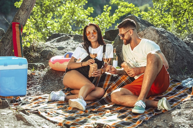 Young couple having picnic at riverside in sunny day. woman and man spending time on the nature together. having fun, eating, playing and laughting. concept of relationship, love, summer, weekend. Free Photo