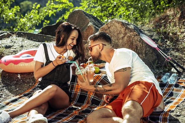 Giovani coppie che hanno picnic in riva al fiume nella giornata di sole
