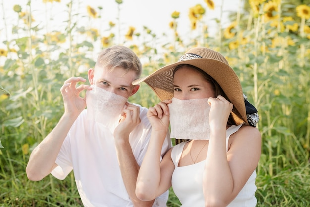 Young couple having picnic on sunflower field at sunset, making funny faces