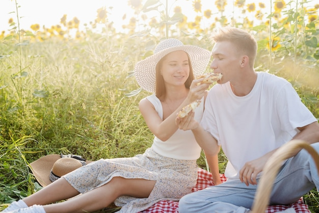Young couple having picnic on sunflower field at sunset