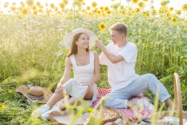 Young couple having picnic on sunflower field