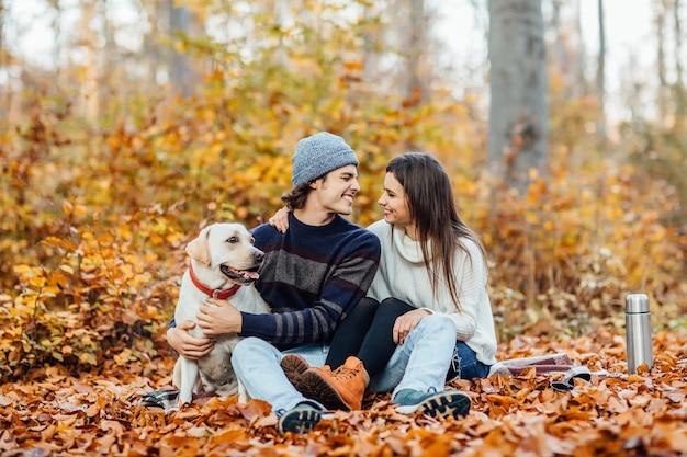 毛布の上に座って、公園で飲み物と彼らの黄金のラブラドールとピクニックをしている若いカップル
