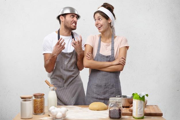 Giovani coppie che hanno litigare durante la cottura in cucina.