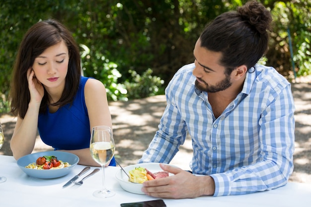 Young couple having relationship difficulties at outdoor restaurant