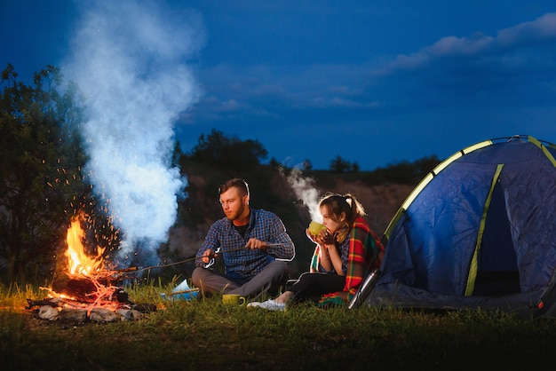 Young couple having a rest at bonfire beside camp and blue tourist tent, drinking tea, enjoying night sky.