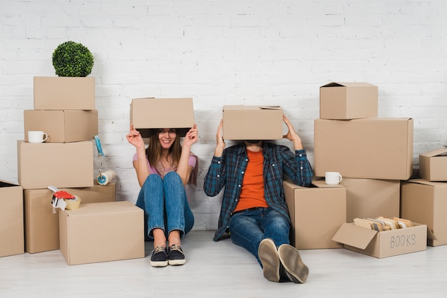 Young couple hiding their face sitting between the cardboard boxes in their new house