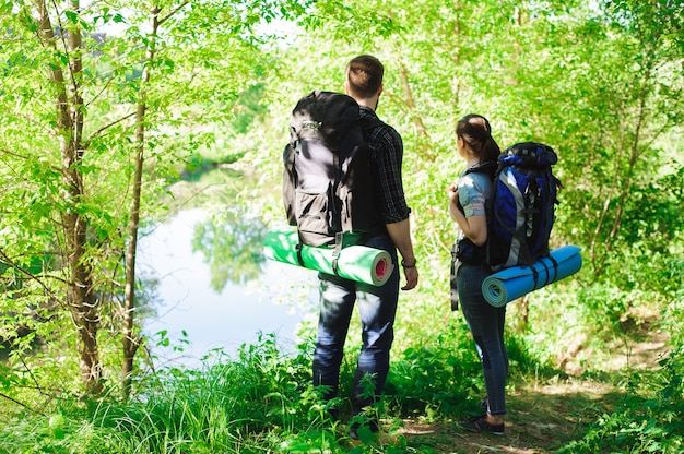 Young couple hikers in forest. sports man and woman with backpacks on road in nature.