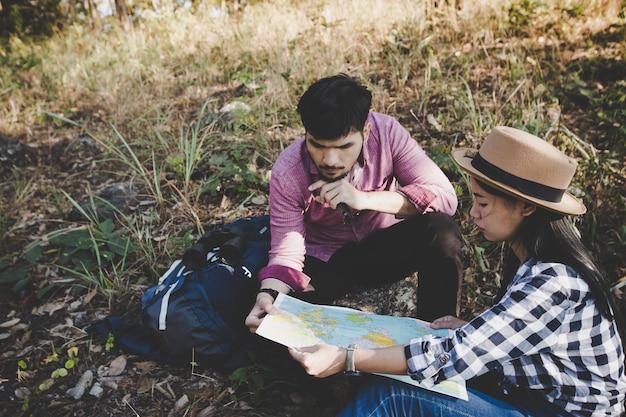 若いカップルのハイカーと地図を見て道を見いだす