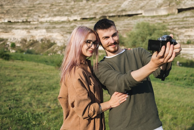Young couple hiking taking selfie  happy young man and woman taking self portrait with mountain scenery