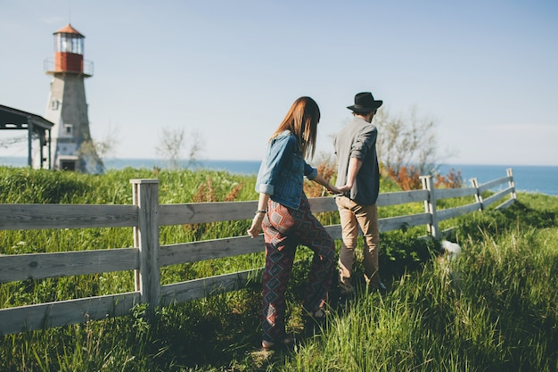Young couple hipster indie style in love walking in countryside, holding hands, lighthouse on background, warm summer day, sunny, bohemian outfit, hat