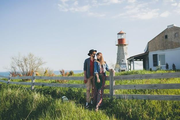 Giovane coppia hipster stile indie innamorato che cammina in campagna, tenendosi per mano, faro sullo sfondo, calda giornata estiva, soleggiato, vestito bohémien, cappello