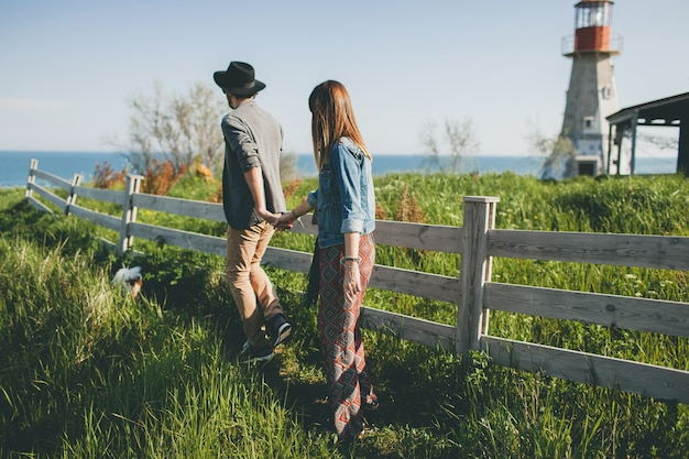 Young couple hipster indie style in love walking in countryside, holding hands