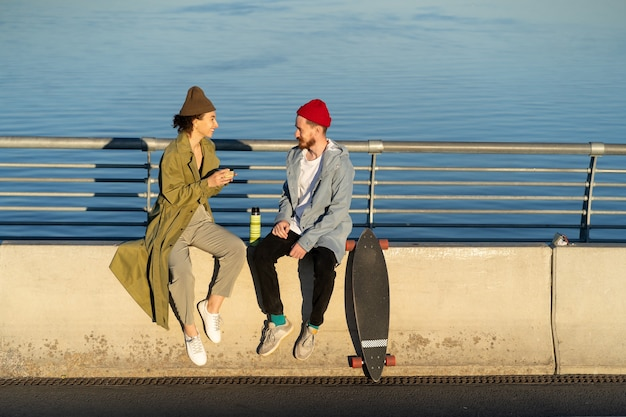 Young couple of hipsters enjoy time together sit on bridge at river drink hot tea from thermos talk
