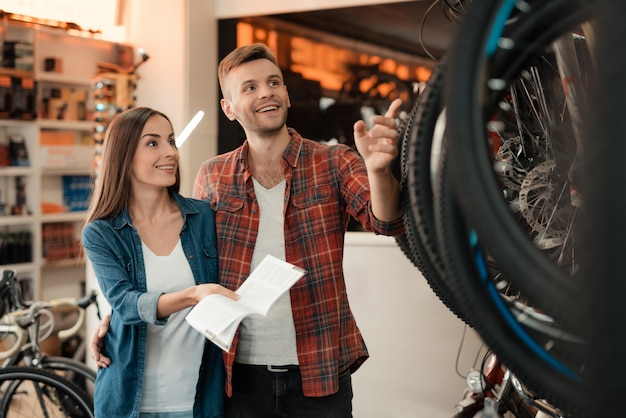 Young couple hold catalog choose new bicycle.