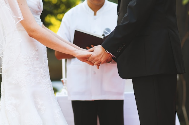 Young couple hold hand at wedding ceremony