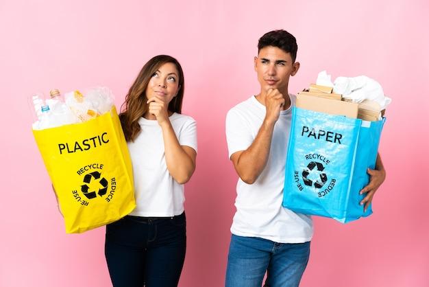 ピンクのプラスチックと紙でいっぱいのバッグを持って見上げる若いカップル