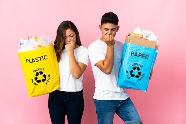 Молодая пара, держащая сумку, полную пластика и бумаги на розовом, сомневается