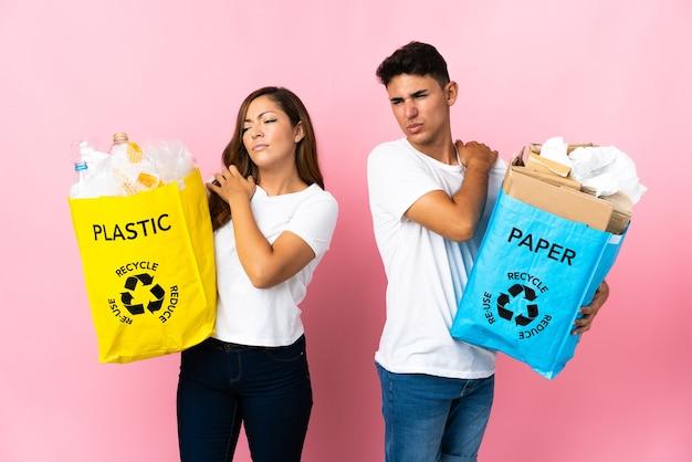 노력을 한 것에 대한 어깨 통증으로 고통받는 분홍색에 플라스틱과 종이로 가득 찬 가방을 들고 젊은 부부