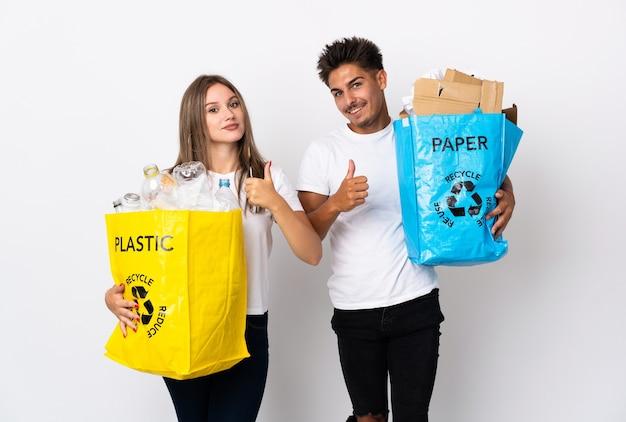Молодая пара держит мешок, полный пластика и бумаги на белом, показывает палец вверх