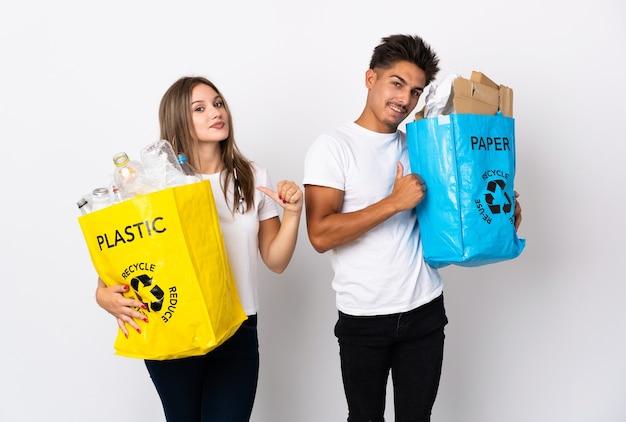Молодая пара держит мешок, полный пластика и бумаги на белом, гордый и самодовольный