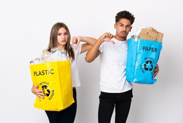 Молодая пара держит мешок, полный пластика и бумаги на белом, показывает палец вниз с негативным выражением лица