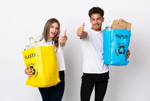 Молодая пара держит мешок, полный пластика и бумаги на белом, пальцы вверх, потому что произошло что-то хорошее