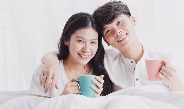 행복한 표정으로 침대에 앉아 커피 한 잔을 들고 젊은 부부
