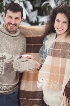 Молодая пара держит горячий чай в зимнем парке
