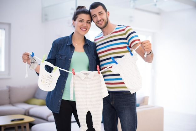 Young couple holding baby bodysuits at home