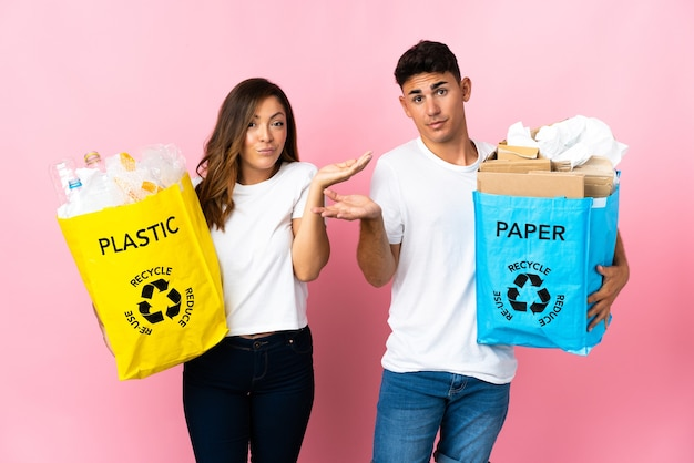 Young couple holding a bag full of plastic and paper on pink having doubts while raising hands
