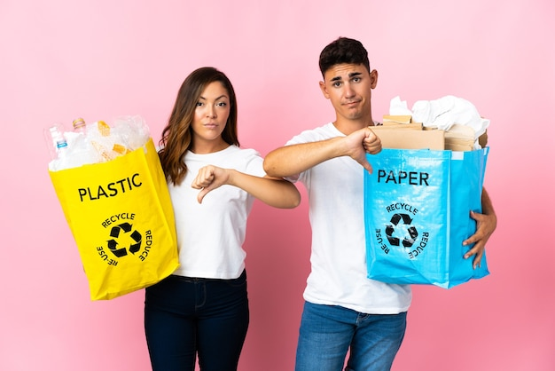 Young couple holding a bag full of plastic and paper on pink showing thumb down with negative expression