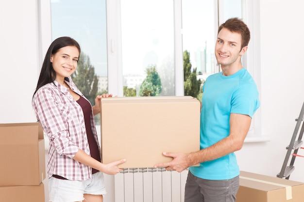 Молодая пара держит большую коробку и счастливо улыбается в камеру в новом доме